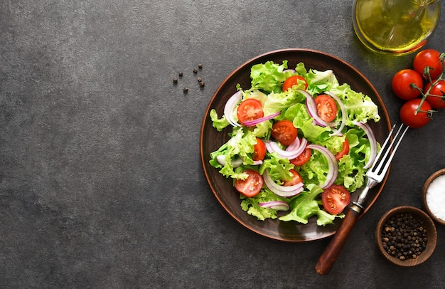 Groentesalade met tomaten, rode uien en saus op zwart, bovenaanzicht