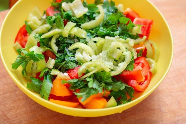 Groentesalade met verse tomaten, paprika's en peterselie in een gele kop. heerlijk gezond tussendoortje.