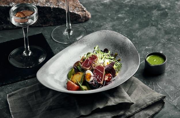 Groentesalade met verse tonijn en avocado citrus in een grijze plaat op een grijze leisteen