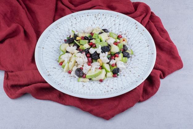 Groentesalade met zwarte olijven en granaatappelpitjes