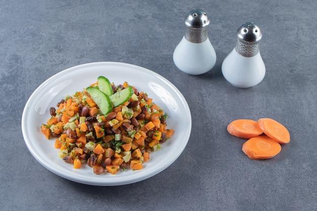 Groentesalade op een bord naast gesneden wortelen en zout op het marmeren oppervlak