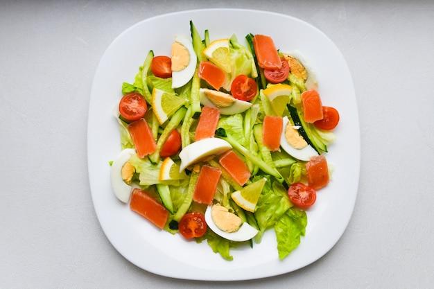 Groentesalade op een witte plaat. verse salade met ei, tomaten, spinazie en avocado op een witte houten oppervlak bovenaanzicht. gezond eten.