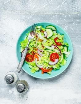 Groentesalade. salade van komkommers, tomaten en rode uien met kruiden en olijfolie. op een rustieke achtergrond.