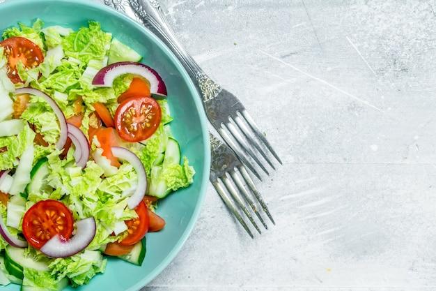 Groentesalade. salade van komkommers, tomaten en rode uien met kruiden en olijfolie op rustieke tafel.