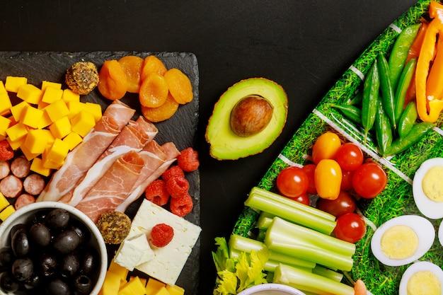 Groenteschotel met vleeswaren bord en avocado.