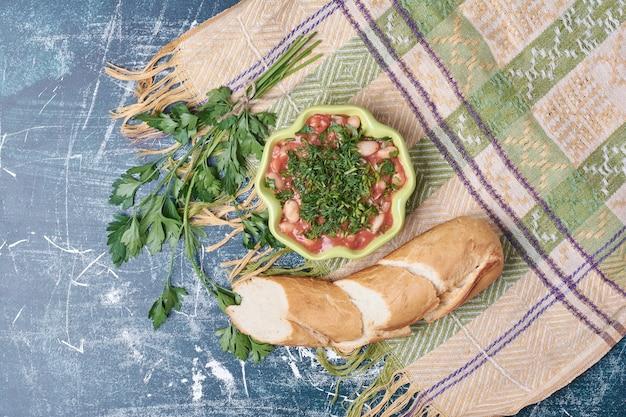 Groentesoep geserveerd met stokbrood, bovenaanzicht.