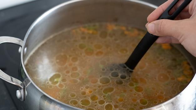 Groentesoep in een pan: wortelen, aardappelen, paprika's, bonen, uien. groenten bereiden op een elektrisch fornuis. de hand van het meisje houdt een lepel vast met heldere gekookte groenten.