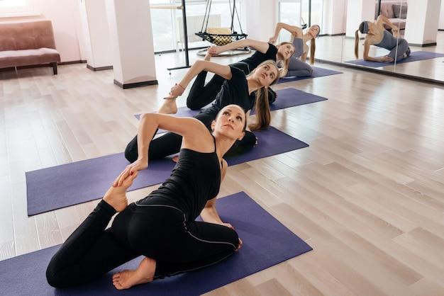 Groep aantrekkelijke sportmeisjes in sportkleding die in fitnesszaal uitwerken.