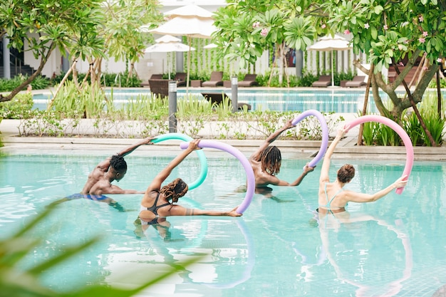 Groep actieve jonge mensen permanent in zwembad met drijvende noedels in handen doen zijbochten, uitzicht vanaf de achterkant