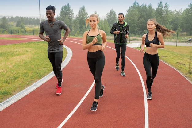 Groep actieve jongens en meisjes in sportkleding renbanen op stadion rennen tijdens de voorbereiding op de marathon