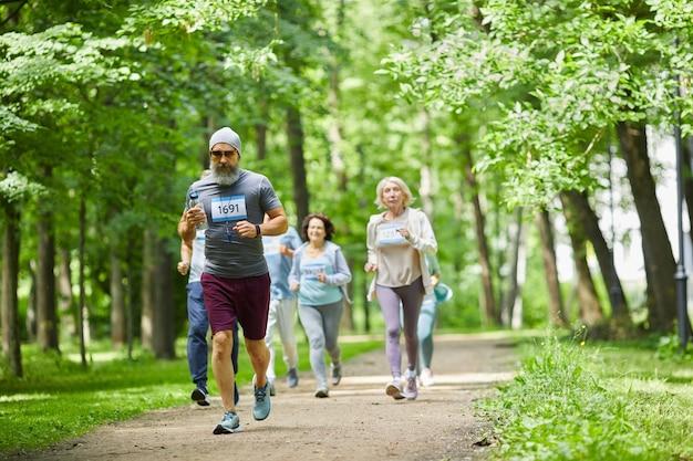 Groep actieve oude mannen en vrouwen die dagtijd doorbrengen in park met marathon, breed schot