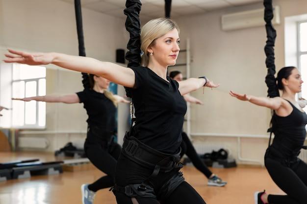 Groep actieve sportmeisjes in zwarte sportkleding houden zich bezig met budgie-fitness in de sportschool