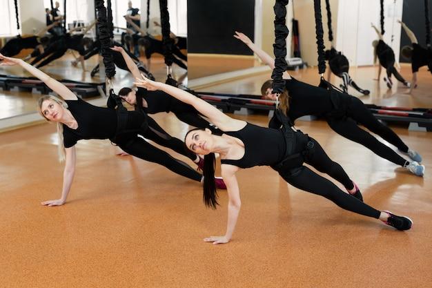 Groep actieve sportmeisjes in zwarte sportkleding houdt zich bezig met parkietfitness in de sportschool. bungeejumpen in de sportschool