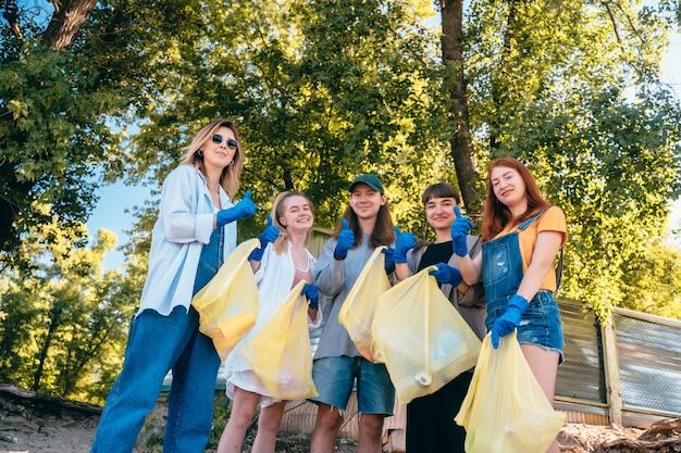 Groep activistenvrienden die plastic afval op het strand verzamelen. jongens tonen hun duim omhoog.