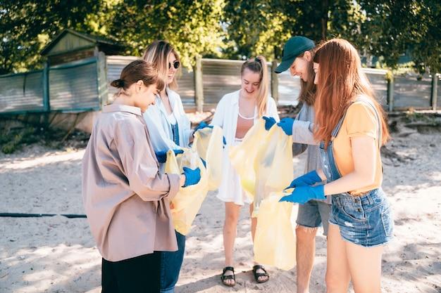 Groep activistenvrienden die plastic afval op het strand verzamelen. milieubehoud.