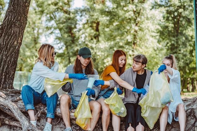 Groep activistenvrienden die plastic afval verzamelen bij het park. milieubehoud.