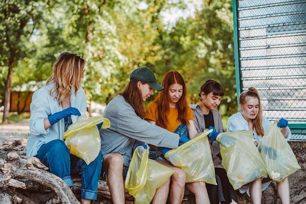 Groep activistenvrienden die plastic afval verzamelen bij het park