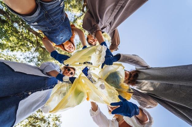 Groep activistenvrienden gooien veel afval in een zak. bottom-up fotograferen