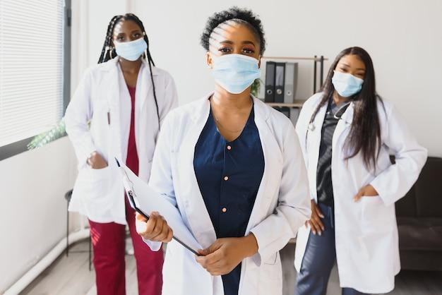 Groep afrikaanse amerikaanse vrouwelijke artsen in beschermende maskers