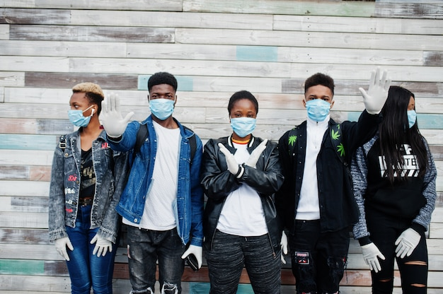 Groep afrikaanse tienersvrienden die medische maskers dragen beschermen tegen infecties en de quarantaine van het coronavirusvirus.