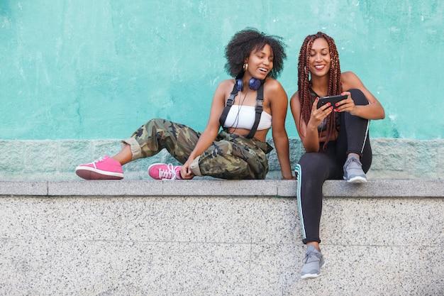 Groep afro amerikaanse vrouwen die technologie op de straat gebruiken
