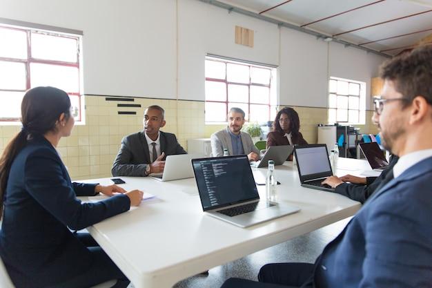 Groep analisten die tijdens ochtendvergadering communiceren