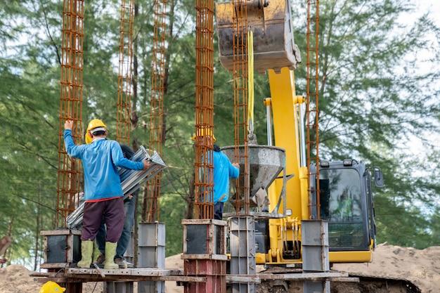 Groep arbeider die een beton gieten bij bouwwerf