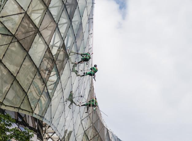 Groep arbeiders die de venstersdienst schoonmaken
