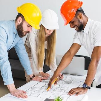 Groep architect die lay-outplan op blauwdruk in het bureau bespreken