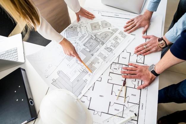 Groep architecten analyseren blauwdruk op tafel