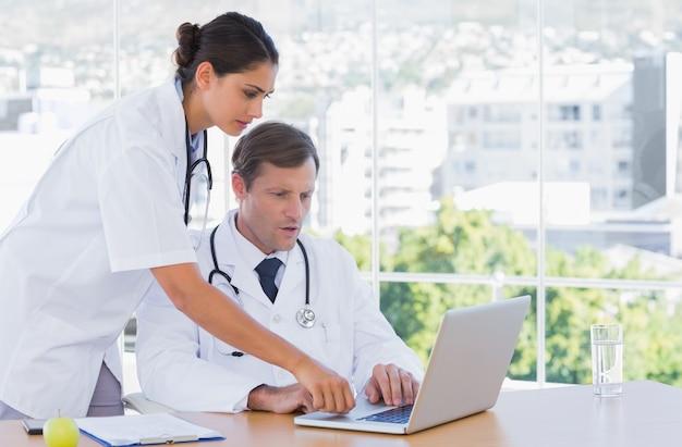Groep artsen die aan laptop samenwerken