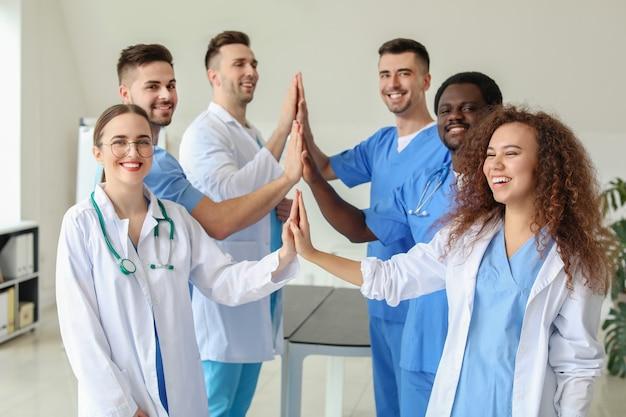 Groep artsen die handen samen in kliniek samenstellen. eenheid concept
