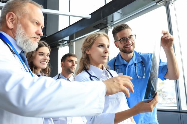 Groep artsen die röntgenfoto's in een ziekenhuis controleren.