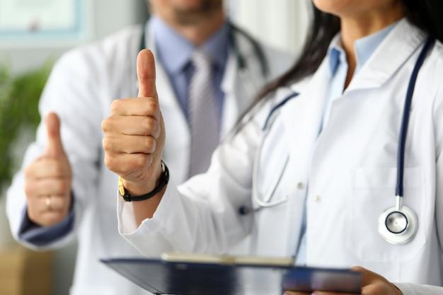 Groep artsen die zich in rij bevinden die duim op symbool tonen