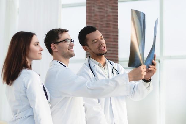 Groep artsen en verpleegsters die röntgenfoto bekijken