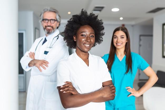 Groep artsen en verpleegsters van gemengde leeftijd die zich zij aan zij bevinden en de camera bekijken.