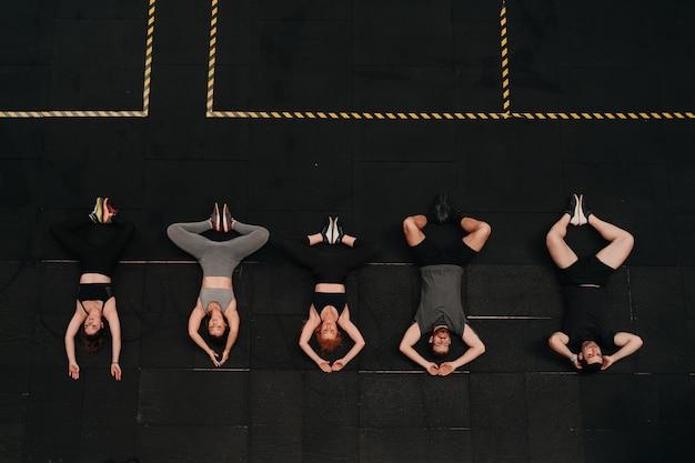 Groep atleten die zich samen uitrekken om de crossfit-trainingsroutine te starten.