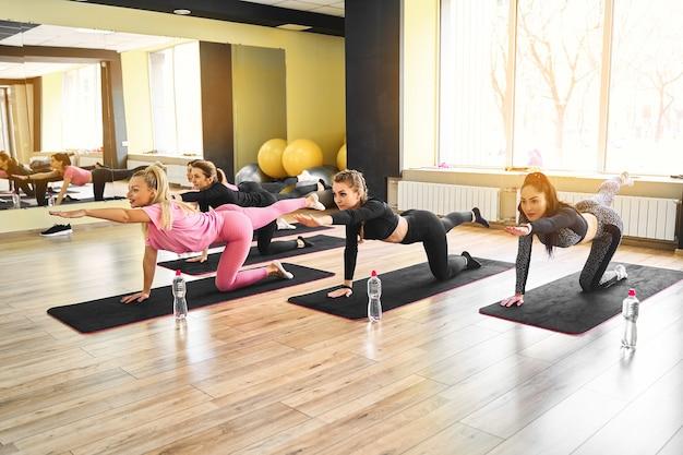 Groep atletische vrouwen doen pushups op de vloer en rekoefeningen in de sportschool
