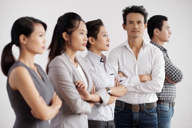 Groep aziatische bedrijfsmensen die in studio met gevouwen wapens stellen