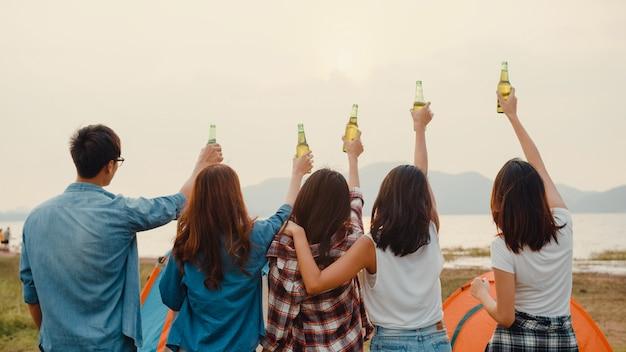 Groep aziatische beste vrienden tieners salueren en proosten toast van flesbier genieten van feest met gelukkige momenten samen in nationaal parkkamp