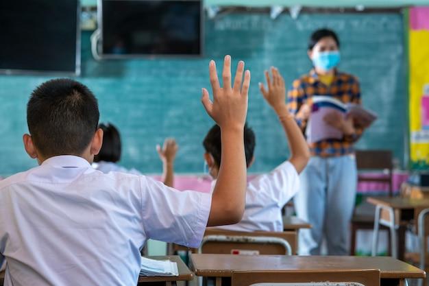 Groep aziatische elementaire studenten die een beschermend masker dragen ter bescherming tegen covid-19, studenten in uniform met leraar die samen in de klas studeren