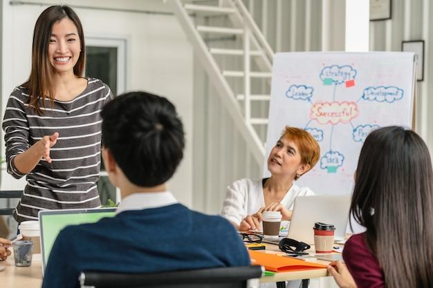 Groep aziatische en multi-etnische zakenmensen met casual pak brainstormen en werken
