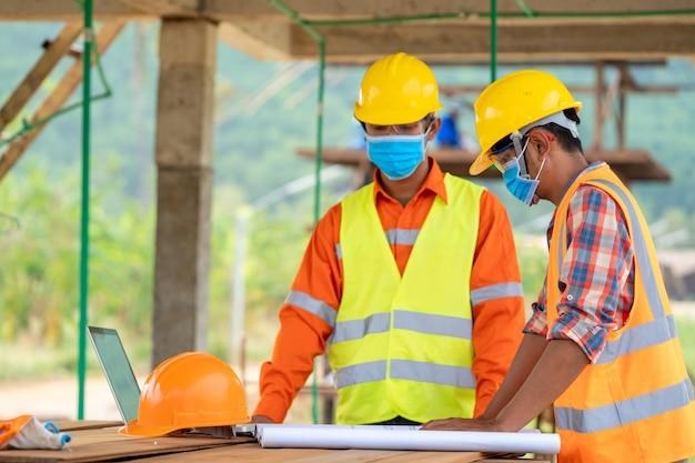 Groep aziatische ingenieurs die een beschermend masker dragen om te beschermen tegen covid-19 met helmveiligheid op de bouwplaats,