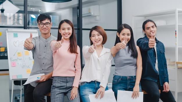 Groep aziatische jonge creatieve mensen in slimme vrijetijdskleding glimlachend en duimen omhoog op creatieve kantoorwerkplek.