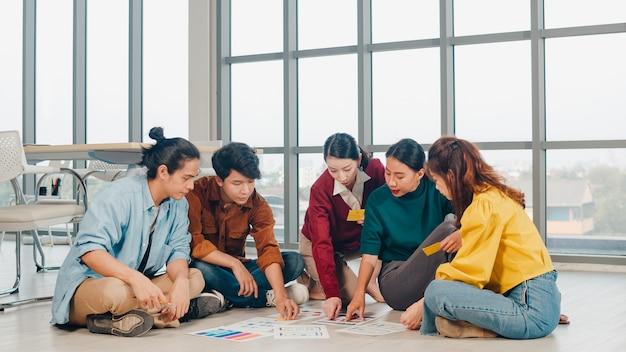 Groep aziatische jonge creatieve mensen in vrijetijdskleding bespreken zakelijke brainstorm vergaderideeën mobiele applicatie software ontwerp projectplan aangelegd op de vloer in kantoor. collega teamwerk concept.