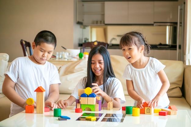 Groep aziatische kinderen die stuk speelgoed samen thuis spelen, aziatisch jonge geitjesconcept