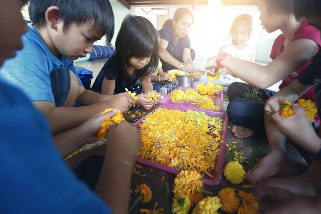 Groep aziatische kinderen leren bloemschikken en plezier thuis.