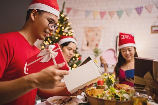 Groep aziatische mensen die thuis een nieuwjaarsfeest hebben. ze openen nieuwjaarsgeschenken.