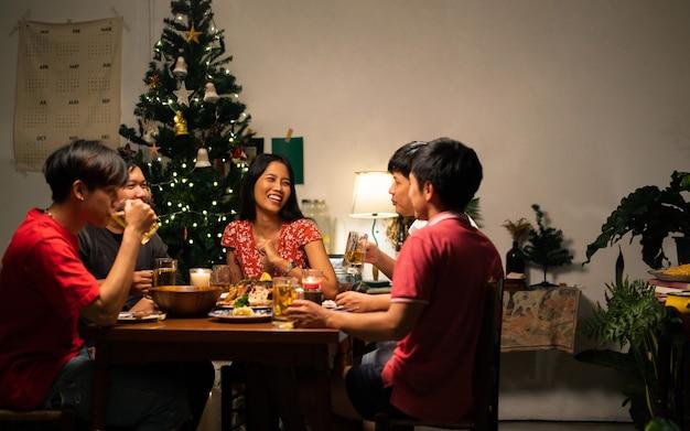 Groep aziatische mensen hebben een etentje en bier thuis