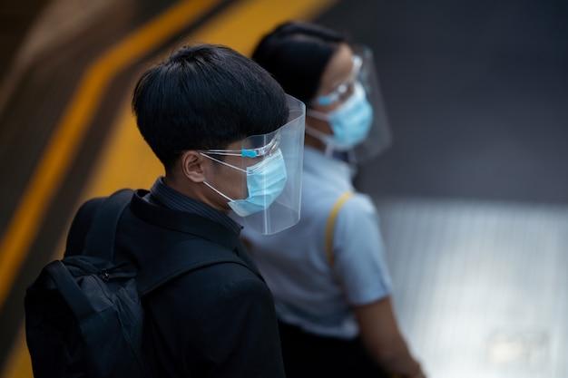 Groep aziatische mensen. ze draagt een gelaatsscherm en een antivirusmasker. ze staan op de roltrap.